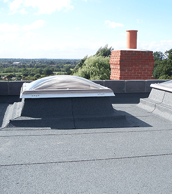 Bailey Classic flat roofing installed on a building around skylights and a chimney